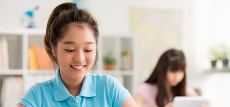 Smiling Asian schoolgirl using digital tablet in the class